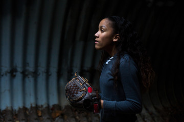Side view of girl wearing softball glove in tunnel