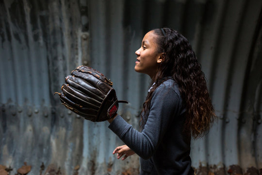 Side view of girl preparing to catch ball in tunnel