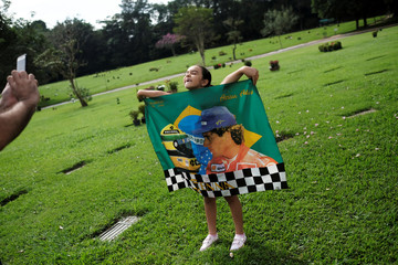 Fan takes a picture of his daughter holding a flag with the image of the  Brazil's Formula One driver Ayrton Senna and his helmet in front of the grave of him, on the 25th anniversary of his death, in Sao Paulo