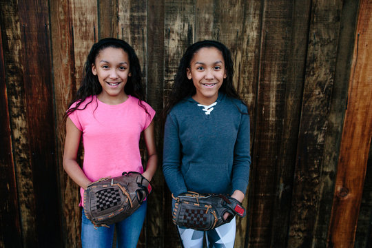 Twin sisters wearing softball gloves smile for the camera