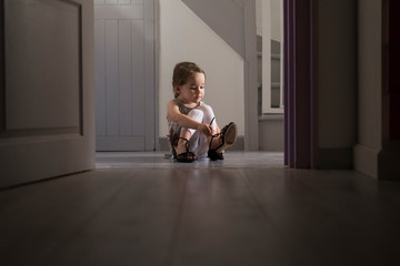 Girl trying on mother's shoe at home