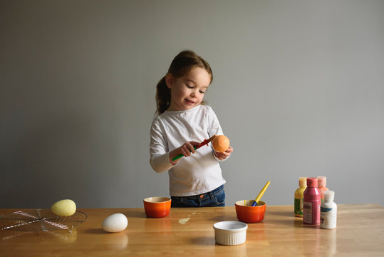 Child paints Easter Eggs at kitchen table craft