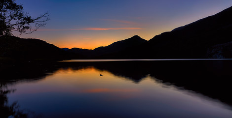 The sun has set behind the mountains around Llyn Gwynant, a lake in Snowdonia (Eryri), Wales (Cymru), UK. Silhouetting the mountains, casting a reflection off of the water.