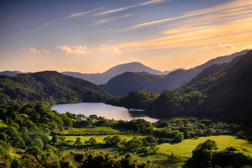 In de dag Lavendel The Sun shining across a mountain and into Llyn Gwynant, Snowdonia (Eryri), Wales (Cymru), UK