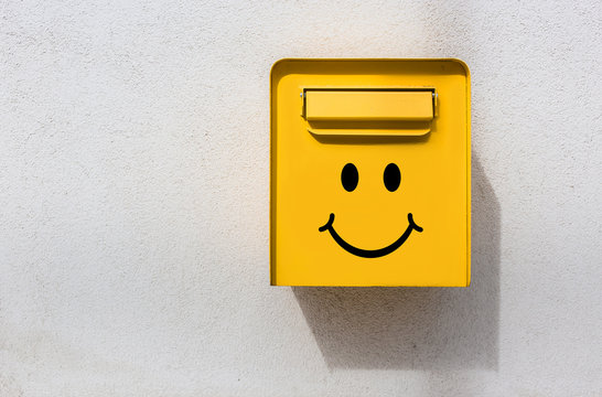 Yellow mailbox on white wall with smiley face on it. Positive vibes, news