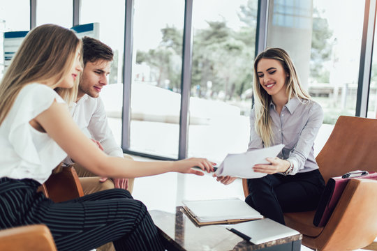 Financial advisor showing report to young couple for their investment. Salesman and positive couple talking about purchase. Happy couple consulting financial agent for loan.