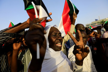 Sudanese protesters wave national flags and make victory signs as they attend a demonstration in front of the Defence Ministry compound in Khartoum