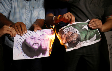 People burn pictures of Masood Azhar, the head of a Pakistan-based militant group Jaish-e-Mohammad, as they celebrate the U.N. Security Council committee's decision to blacklist Azhar, in Ahmedabad
