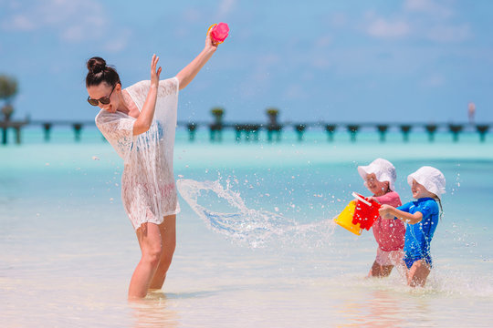 Young mom and little girls having fun during summer beach vacation