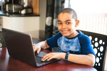 Black boy sitting playing on a laptop computer at home