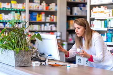 Pharmacist making prescription record through computer in pharmacy. Portrait of female pharmacist working with computer behind counter in pharmacy