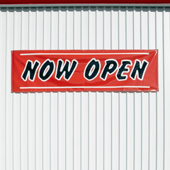 Now Open sign hanging on wall