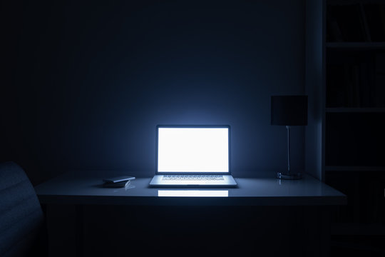 Room illuminated by a computer screen at night, no people. Empty workplace lit by a laptop display in the darkness, late work, overtime concept