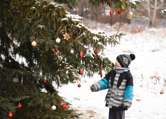 Young boy looking at Christmas decorations on a tree outdoors in snow.