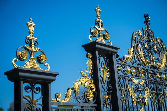 Ornate wrought iron gate with Ornate wrought iron palace gate with royal gold trimming with bright blue sky in London, England, United Kingdom trimming with bright blue sky