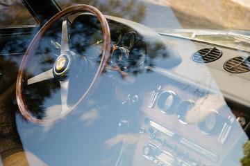 Vintage Ferrari dashboard viewed through window