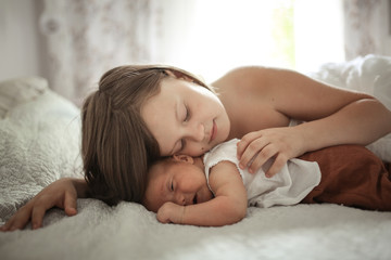 Older sister with baby 1 month, hugging newborn