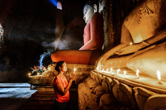 Asian woman lighting candle in temple