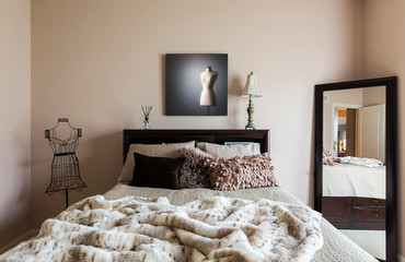 Mirror, bed and dress form in modern bedroom