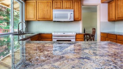 Granite counter reflecting kitchen cabinets