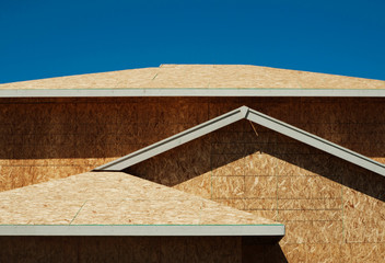 Low angle view of chip board walls of house under construction