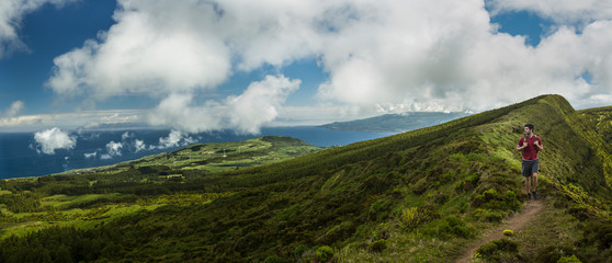 Hiker walking on hilltop dirt path over Cabeco Gordo crater, Faial, Portugal