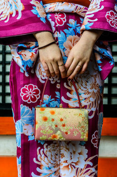 Midsection shot of Japanese woman in kimono holding purse