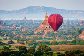 Hot air balloon flying over towers