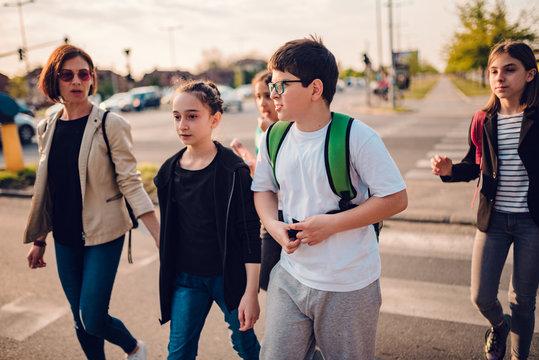 Group of school children crossing road