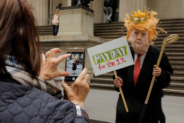A woman takes a photograph of a protester wearing a mask in front of Federal Hall during a May Day rally on Wall Street in Manhattan in New York City