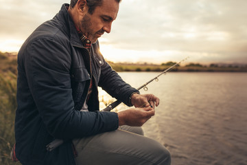 Man sitting near a lake with fishing rod Wall mural
