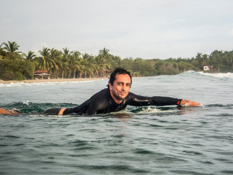 A surfer paddling out in the lineup