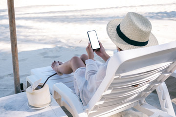 Mockup image of a woman holding white mobile phone with blank desktop screen while laying down on...