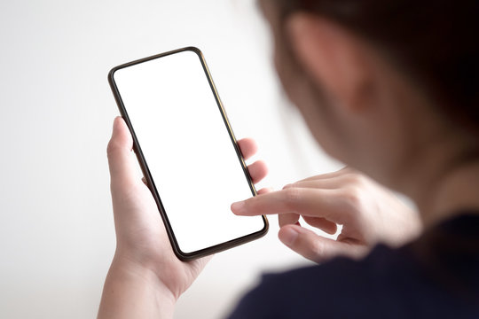Woman hands using smartphone mockup at the white office desk. Blank screen mobile phone for graphic display montage