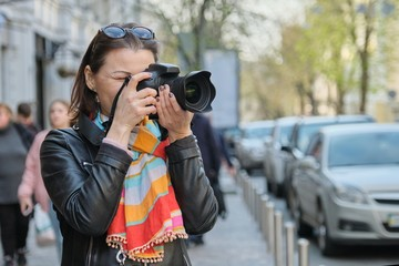 Mature woman with photo camera photographing on the street of spring city, female professional photographer,copy space