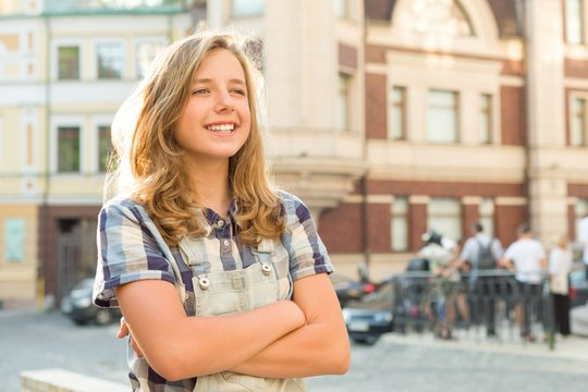 Outdoor portrait of smiling teenager girl 12, 13 years old on city street, girl with folded hands, copy space