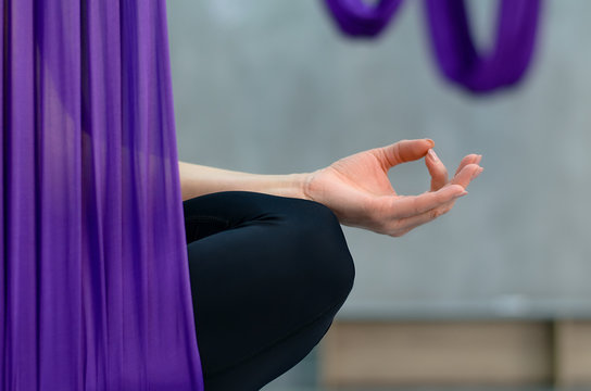 Aerial yoga or fly yoga. Woman sitting in lotus pose in hammock with hand doing zen gesture or mudra. Healthy lifestyle concept. Close up shot, copy space