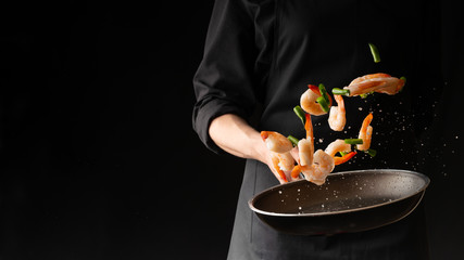 Photo sur Plexiglas Nourriture Seafood, Professional cook prepares shrimps with sprigg beans. Cooking seafood, healthy vegetarian food and food on a dark background. Horizontal view. Eastern kitchen