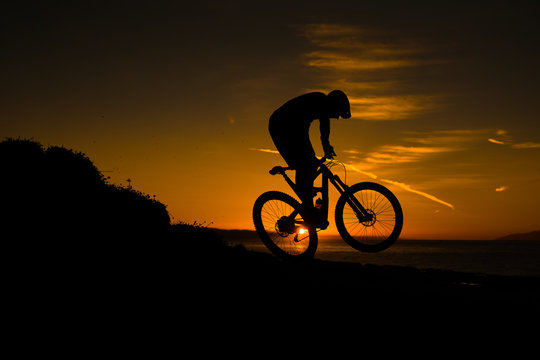 silhouette of cyclist on background of sunset sky