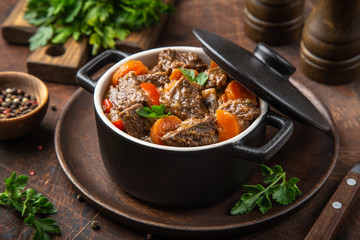 beef stew with vegetables in black pot on dark wooden background,