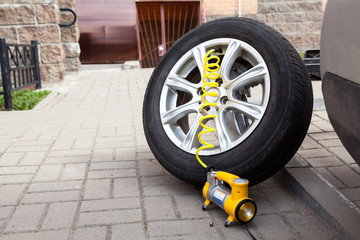 Dismounted car wheel ready for inflate a tyre with pneumatic pump, copyspace