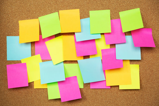 collection of colorful variety post it. paper note reminder sticky notes pad on cork bulletin board. empty space for text. soft focus.
