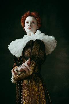 Look of pride. Medieval redhead young woman in golden vintage clothing as a duchess standing crossing hands on dark green background. Concept of comparison of eras, modernity and renaissance.