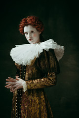 Meditations or thoughts. Medieval redhead young woman in golden vintage clothing as a duchess standing crossing hands on dark green background. Concept of comparison of eras, modernity and renaissance