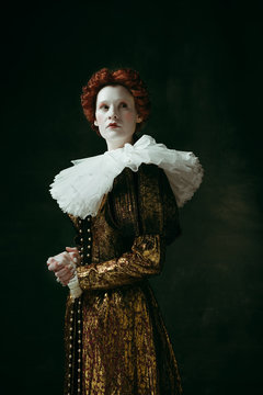 No fear for future. Medieval redhead young woman in golden vintage clothing as a duchess standing crossing hands on dark green background. Concept of comparison of eras, modernity and renaissance.