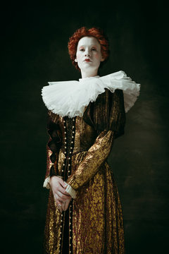 Attention and serious. Medieval redhead young woman in golden vintage clothing as a duchess standing crossing hands on dark green background. Concept of comparison of eras, modernity and renaissance.