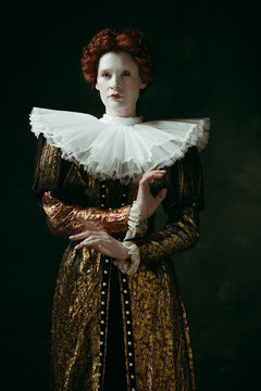 Flexibility of control. Medieval redhead young woman in golden vintage clothing as a duchess standing crossing hands on dark green background. Concept of comparison of eras, modernity and renaissance.