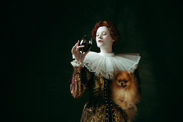 Wanna try. Medieval redhead young woman in golden vintage clothing as a duchess holding puppy and glass with red wine on dark green background. Concept of comparison of eras, modernity and renaissance Wall mural