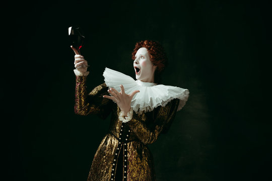 Better than others. Medieval redhead young woman in golden vintage clothing as a duchess holding a glass with red wine on dark green background. Concept of comparison of eras, modernity and