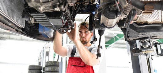 Automechaniker in Werkstatt repariert Fahrzeug // car mechanic in work clothes works in a workshop and repairs a vehicle